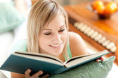 Bright woman reading a book lying on a sofa — Stock Photo