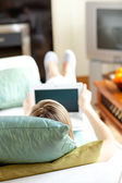 Blond woman using a laptop lying on a sofa — Stock Photo