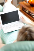 A woman using a laptop lying on a sofa — Stock Photo