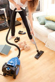 Young woman vacuuming the living-room — Stock Photo