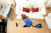 High angle of a blond woman vacuuming — Stock Photo