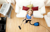 High angle of a happy woman vacuuming — Stock Photo