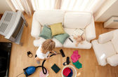 Blond woman vacuuming the living-room — Stock Photo
