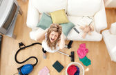 Stressed blond woman vacuuming the living-room — Stock Photo