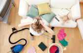 Depressed blond woman vacuuming the living-room — Stock Photo