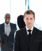 Serious businessman in front of his team — Stock Photo