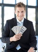 Businessman holding dollars — Stock Photo