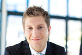 Young businessman smiling at the camera — Stock Photo