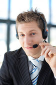 Young businessman with a headset on in a call center — Stock Photo
