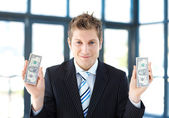 Attractive businessman holding dollars — Stock Photo