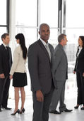 Serious business leader looking at camera in front of team — Stock Photo