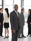Business leader looking at camera in front of team — Stock Photo