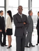Business man looking at camera with group in background — Stock Photo