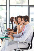 Smiling African-American businesswoman working in a call center — Stock Photo