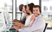 Smiling businessman working in a call center — Stock Photo