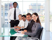 Business in a meeting smiling at the camera — Stock Photo