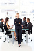 Friendly businesswoman smiling at the camera in a meeting — Stock Photo