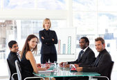 Serious businesswoman looking at the camera with her team — Stock Photo