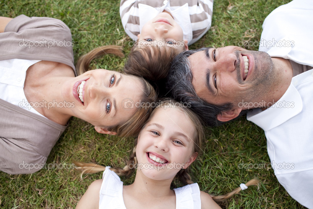 Smiling family lying outdoors with heads together — Stock Photo #10300077