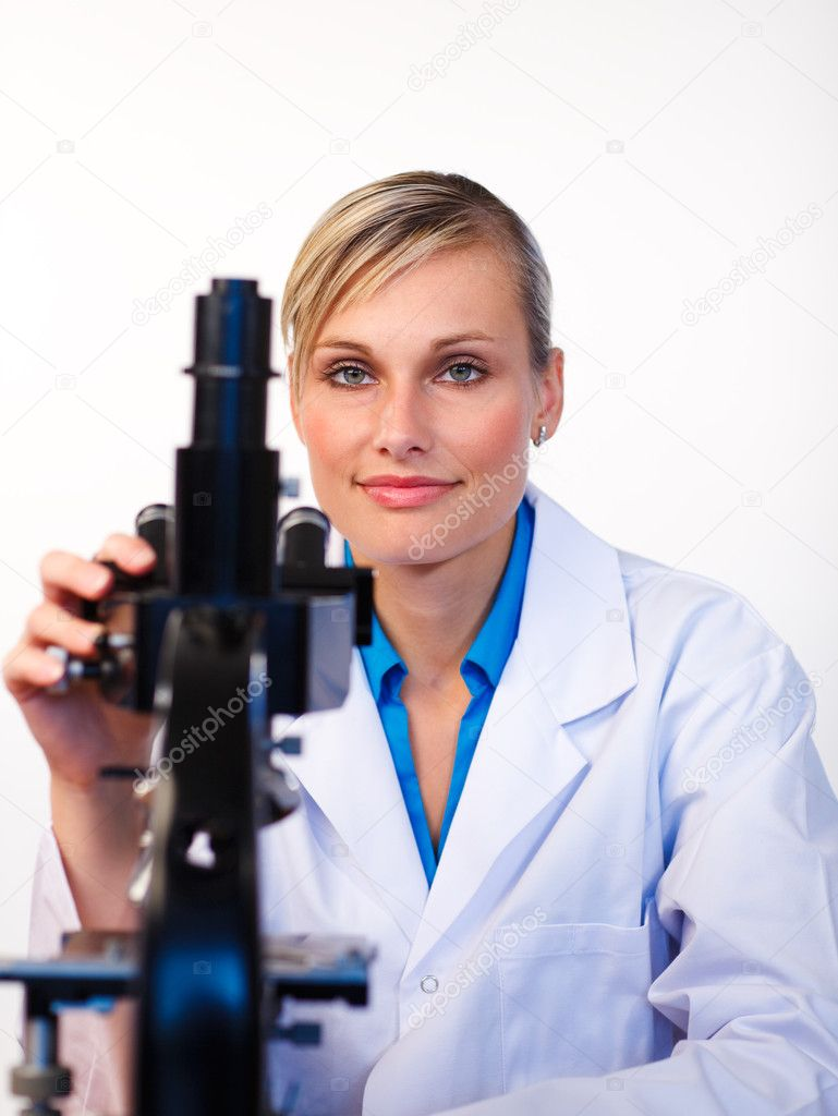 Beautiful scientist working with a microscope looking at the camera  Stock Photo #10302508