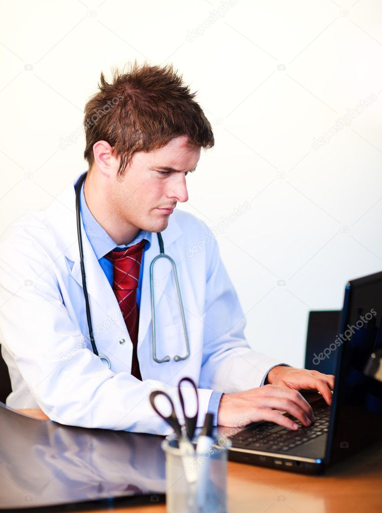Thoughtful handsome doctor working on a computer in hospital — Stock Photo #10302719