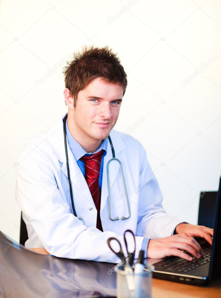 Smiling young doctor working on a computer in hospital — Stock Photo #10302724