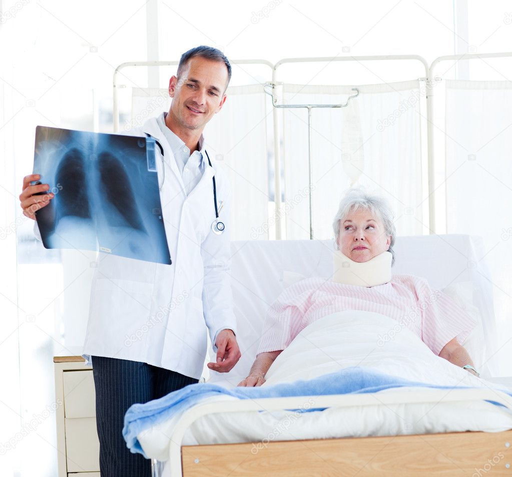 A doctor showing an x-ray to a patient with a neck brace — Stock Photo #10304251