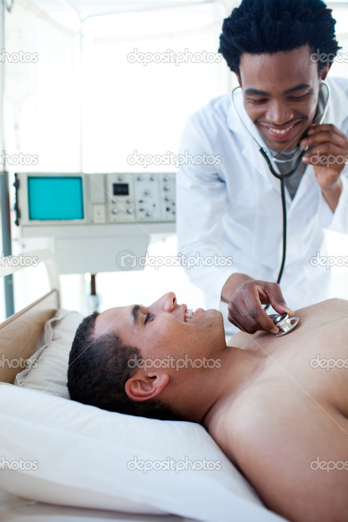 Smiling doctor checking the pulse on a male patient lying on a hospital bed  Stock Photo #10304282