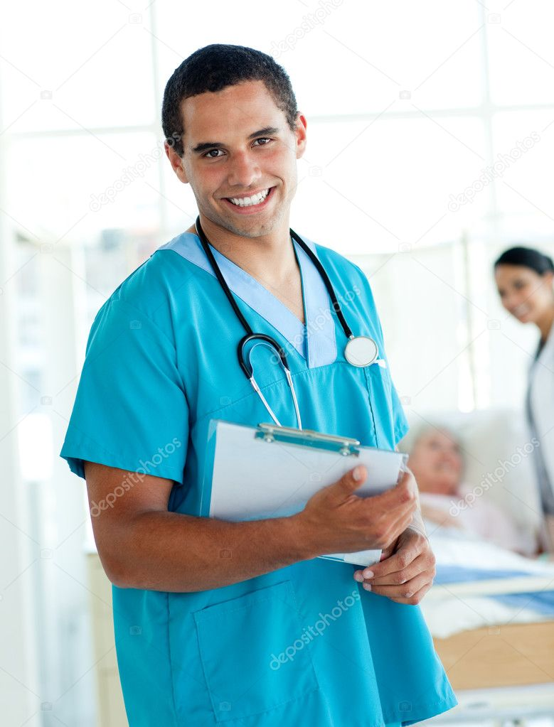 Attractive male doctor holding a medical clipboard in a hospital  Stock Photo #10304301