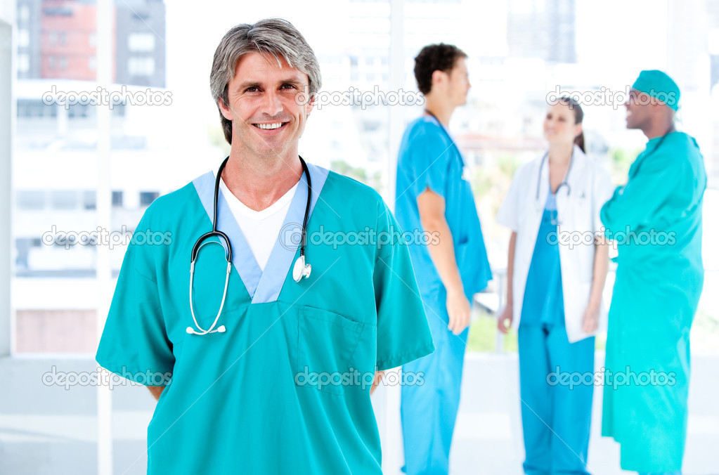 Joyful male doctor looking at the camera while his medical partners talking together in the hospital — Stock Photo #10304570