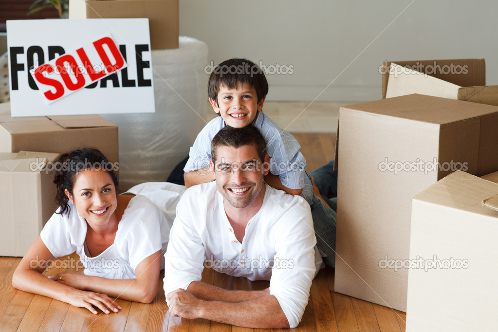 Happy parents and son lying on the floor after buying new house — Stock Photo #10307940