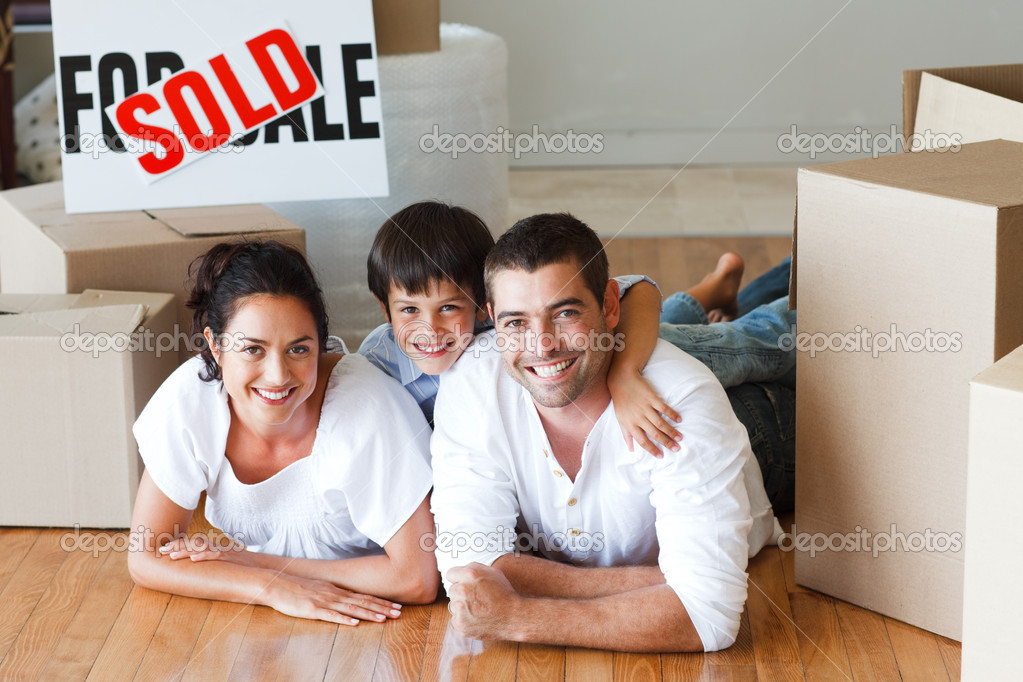 Happy family lying on the floor after buying new house with boxes — Stock Photo #10307953
