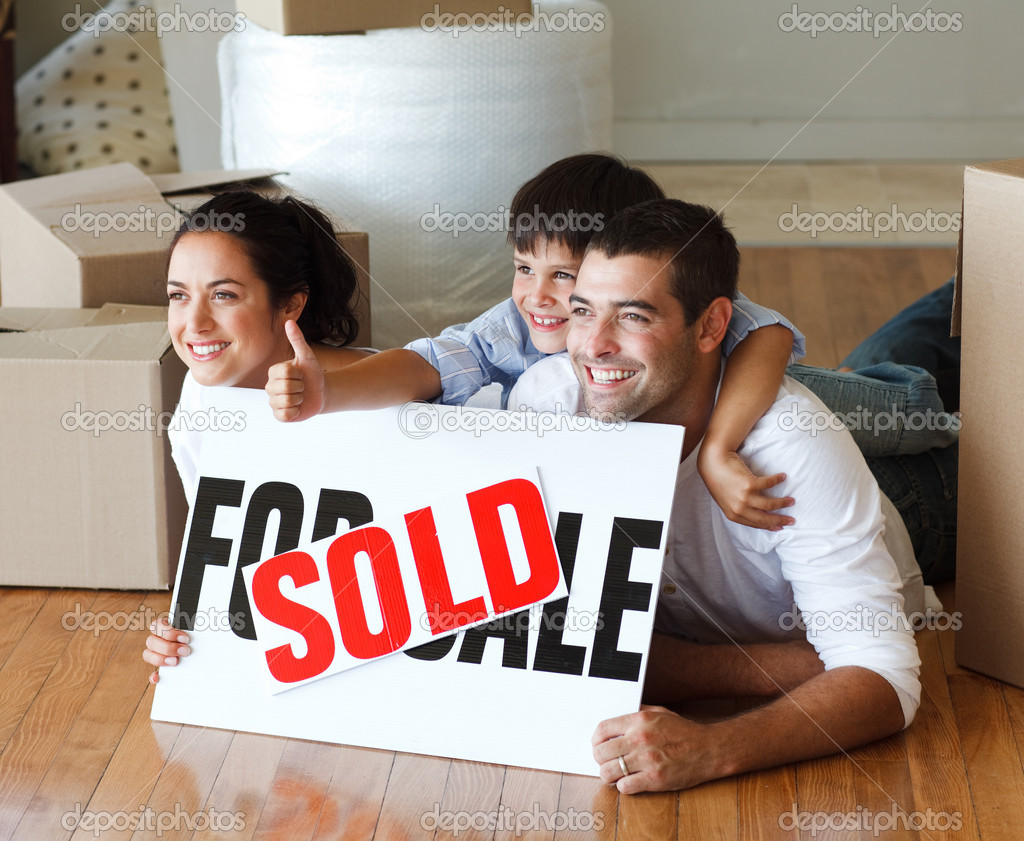 Happy family lying on the floor after buying new house with thumbs up — Stock Photo #10307968