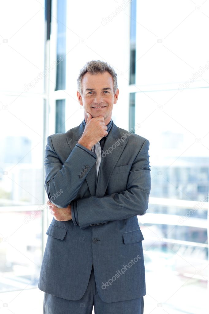 Smiling senior businessman standing in office — Stock Photo #10308825