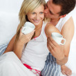 Couple in bed drinking coffee with affection - Stock Photo