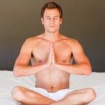 gut aussehender Mann auf dem Bett mit Clossed Augen meditieren — Stockfoto