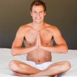 Smiling man meditating on bed — Stock Photo