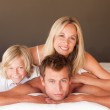 Happy couple and son enjoying together in bed — Stock Photo