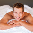 Attractive man smiling on bed — Stock Photo