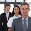 Mature businessman leading a business team in a line  — Stock Photo