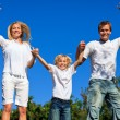 Stock Photo: Happy family Jumping in air