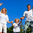 Young family jumping in the air against thr blue sky — Stock fotografie