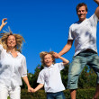 Cute family jumping in the air — Stock Photo