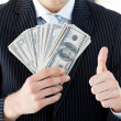 Businessman showing dollars with thumbs up - Foto Stock