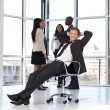 Manager relaxing in office with team in background — Stock Photo #10310592