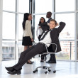 Manager relaxing in office with team in background — Stock Photo