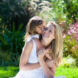 Foto Stock: Little girl kissing her mother