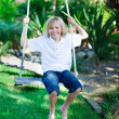Kid having fun on a swing — Stock Photo