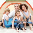 Family camping on beach playing a guitar — Stockfoto