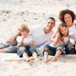 Family playing sitting on a beach — Stock Photo